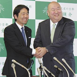 松尾市長(左)と笑顔で握手を交わす久保田社長(右)=5月15日、市役所