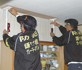 突っ張り棒を設置するガーディアンズのメンバー。天井に当て板をし家具の下にはストッパーも取り付ける