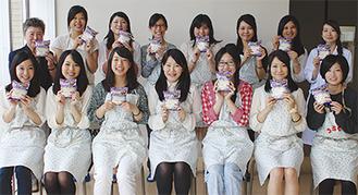 考案した商品を手にする学生ら。後列左端は浦川教授。後列右端は庄谷洋美助手=5月22日、同大学