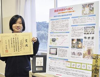 研究成果を記したパネルと賞状を手にする矢澤部長