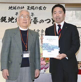 山田会長(左)が『風土記』を松尾市長に手渡した=1月26日(同会提供)