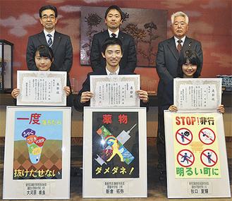 受賞作のポスターと共に前列左から、大河原さん、新倉さん、牧口さん