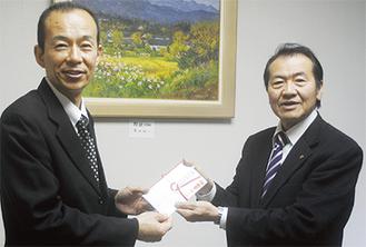 収益金を渡す三橋支部長(右)