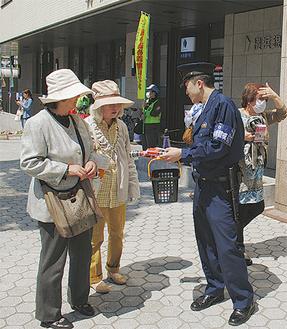 注意を呼びかけながらチラシを配布=4月15日、鎌倉駅東口