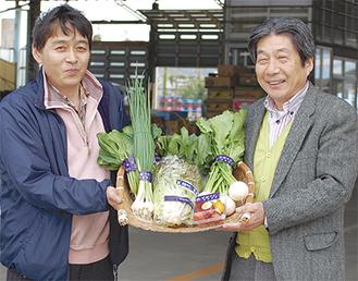 「鎌倉いちばブランド」の野菜を手に取る須田部長(左)と高橋社長(右)