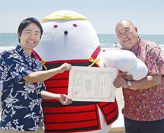 松尾市長に「命名証」を手渡す久保田社長(右)=17日、ビーチフェスタ会場で