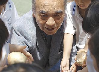 園児たちに玉ねぎを手渡す福井会長