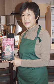 「舞鶴コーヒー」を手に持つ新居さん