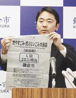 20リットルの有料袋を手にする松尾崇市長