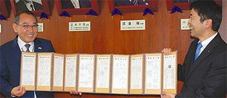 儒教の教えが書かれた記念品を渡す鄭副市長(左)