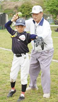 「投球ゲージ」を付けた選手にフォームを指導する清水さん