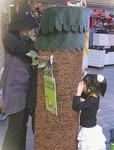 「ぴぴ☆しあたー」を観賞する子ども。木の筒を覗くと人形劇が行われている