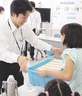 現金1億円の重さを体験する児童