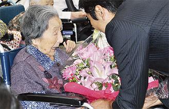 100歳以上の入居者一人ひとりに声をかけながら記念品を手渡す松尾市長(右)。愛の郷では4人が対象となった