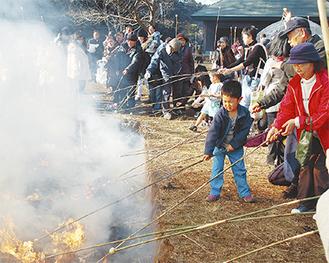 木の枝につけた団子を火にかざす参加者