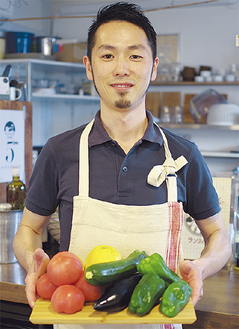 熊本から届いたばかりの食材を持つ山内さん