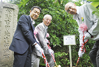 ツバキを植樹する奴田会長(右)と岡会長(中央)