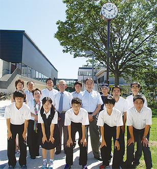 時計をバックに会員と同校の生徒ら