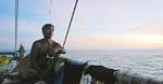 海を見つめるクルー(上)と航海中のホクレア号(=内野さん提供)