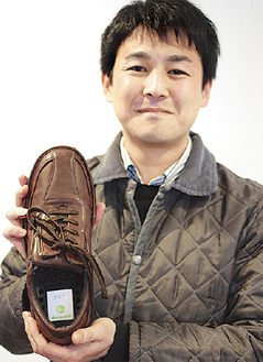 GPS端末を埋め込んだ靴を持つ桂田さん