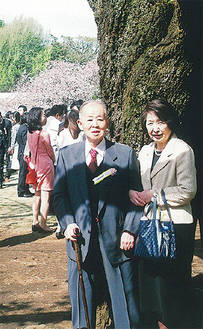 桜の大木の前に立つ高柳さんと妻の澄子さん