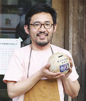 募金箱を手にするコバカバ店主の内堀敬介さん