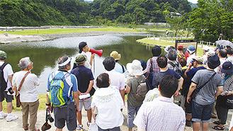 復元された池の説明を受ける参加者