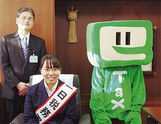 署長席に座る栗原さんと羽生田署長、イータ君