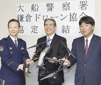 ドローンを手に記念写真に納まる(左から)野口署長、青柳代表、住吉理事
