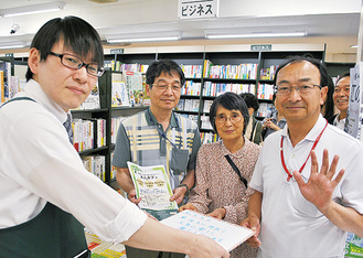 萱野店長(左)に手作りポップを手渡す本人カフェ参加者