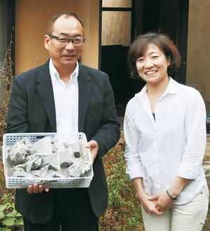 飼料用に加工した海藻を手にする臼井さん(左)と矢野さん