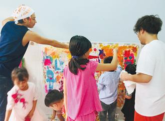 現地の子どもと一緒に絵を描く斉藤さん(右)と野々垣さん