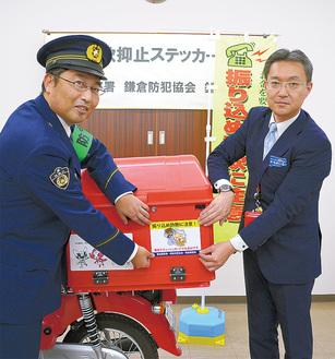 バイクにステッカーを貼る猪俣署長(左)と佐藤局長