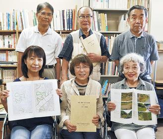 新冊子を手に笑顔の原山幹事(後列中央)とメンバーら