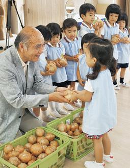 園児に玉ねぎを手渡す福井さん