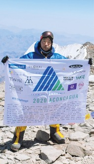 登頂で支援者の氏名を記した旗を掲げる西川さん=西川さん提供
