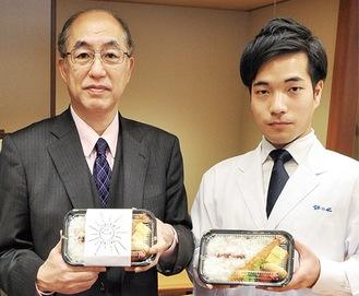 弁当を持つ田中理事長(左)と藤川主任