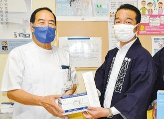 井上院長(左)にマスクを手渡す岡田総代