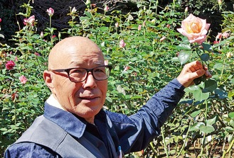 開花したバラと長年維持管理をしてきた荒さん