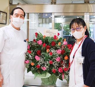 花を受け取り、笑顔を見せる井上院長(左)と島里副院長