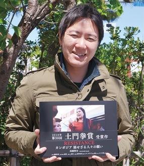 写真集を手にする高橋さん(2019年撮影)