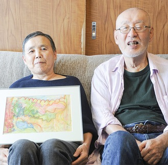 入選作を手にする吉田とめ子さんと夫の龍夫さん