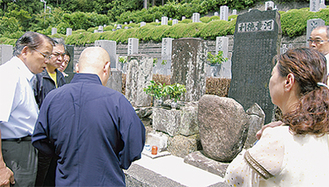 墓と碑の前で住職の話を聞くメンバー