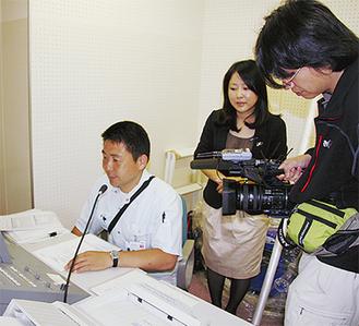 市役所の防災無線室で行われた撮影(中央が通訳の李焱さん)