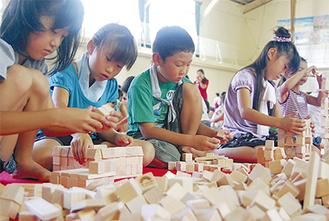 真剣な表情で積み木を組み立てる児童たち