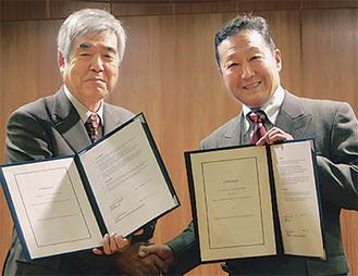 調印式で握手を交わす中山学園長(左)とIFUの北中理事長