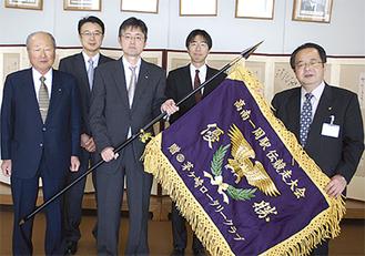 優勝旗を手渡す和田会長(中央)とメンバーら