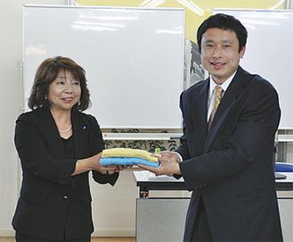 タオルを手渡す飯塚部会長(左)