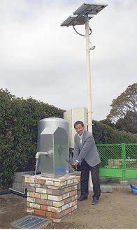 手動ポンプで井戸水を汲み上げる綾さん。後方には太陽光パネルがそびえる