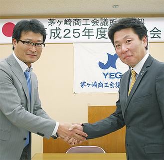 森岡会長(写真右)と握手する原新年度会長(同左)